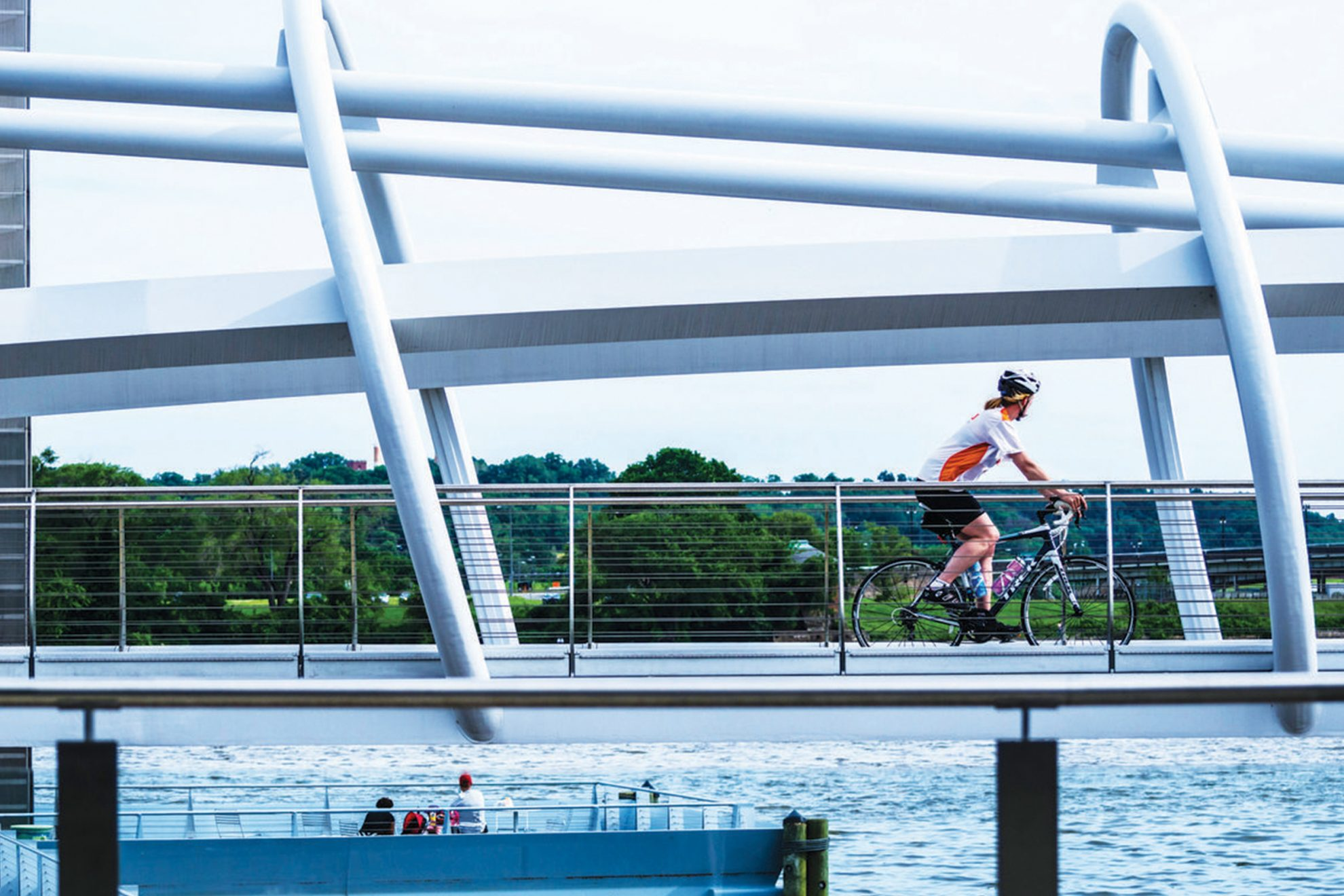 woman on bicycling riding over bridge crossing Anacostia River