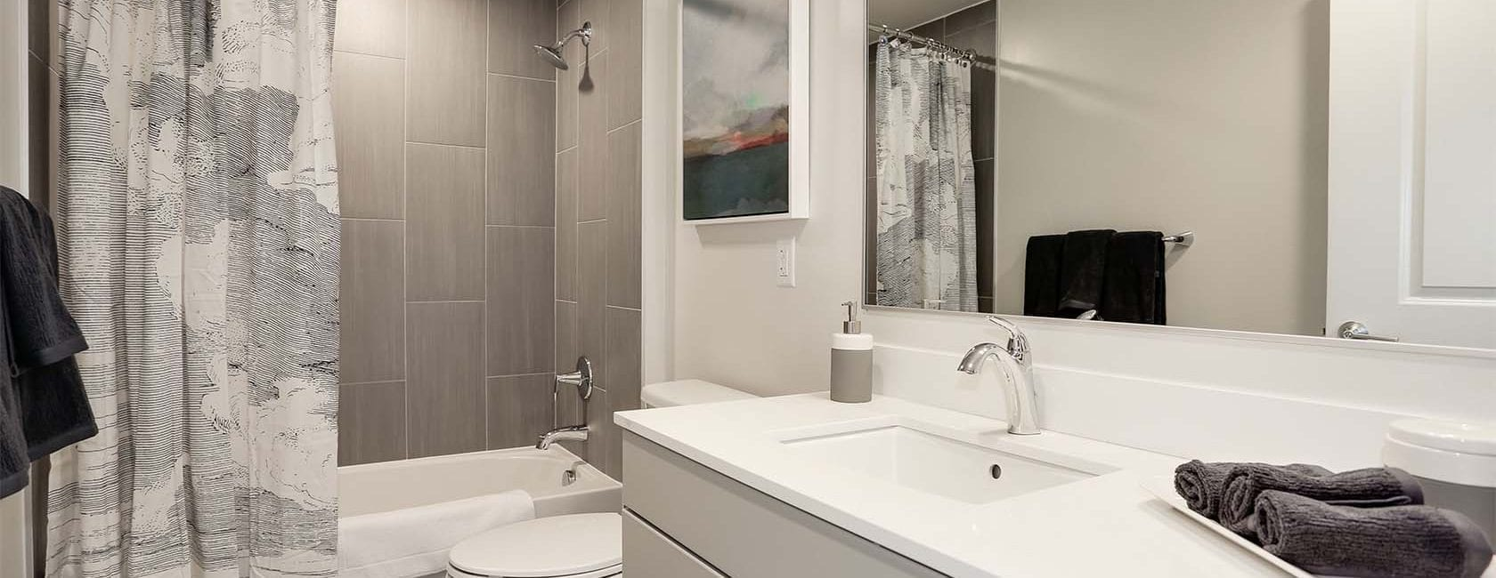 Parc Riverside West Bathroom with tiled bath surrounds, and grey cabinetry with white countertop