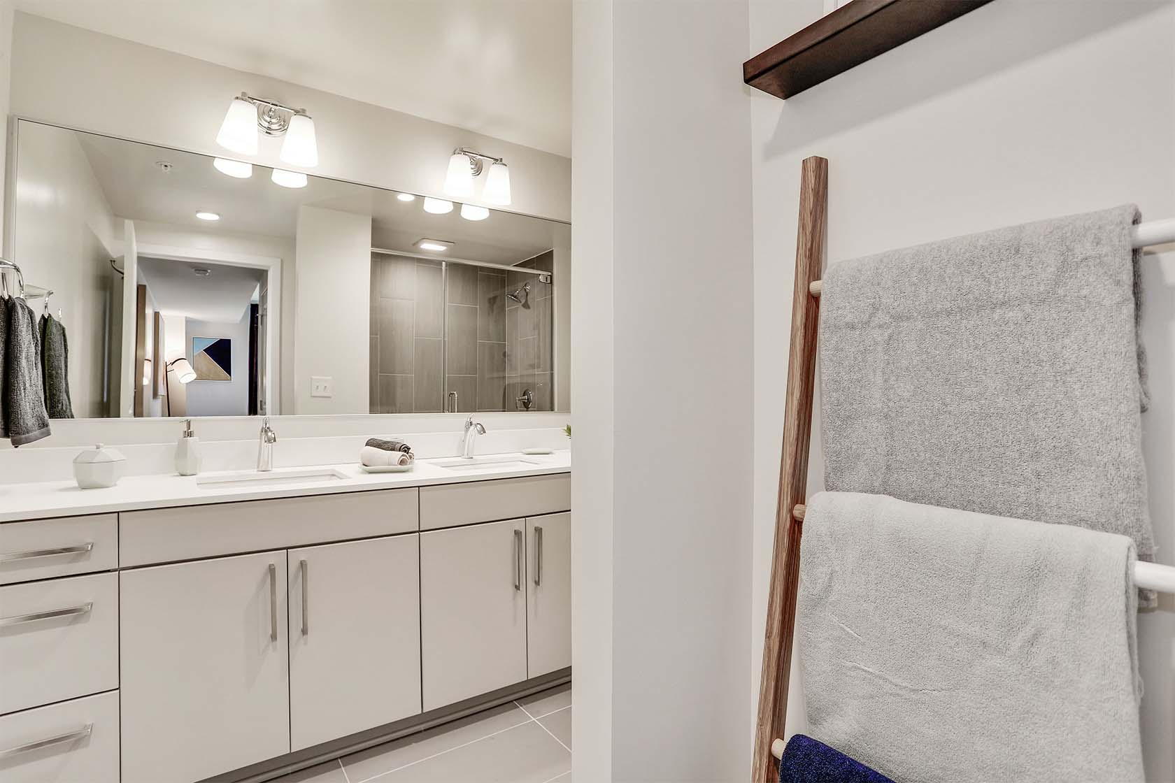 Parc Riverside West bathroom with grey cabinetry, white countertops, double vainty with long mirror, and towel rack