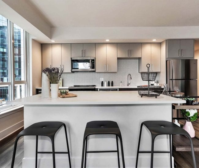 Apartment kitchen at Parc Riverside West with white quartz countertops, kitchen island with three stools, two-tone cabinetry, and stainless steel appliances