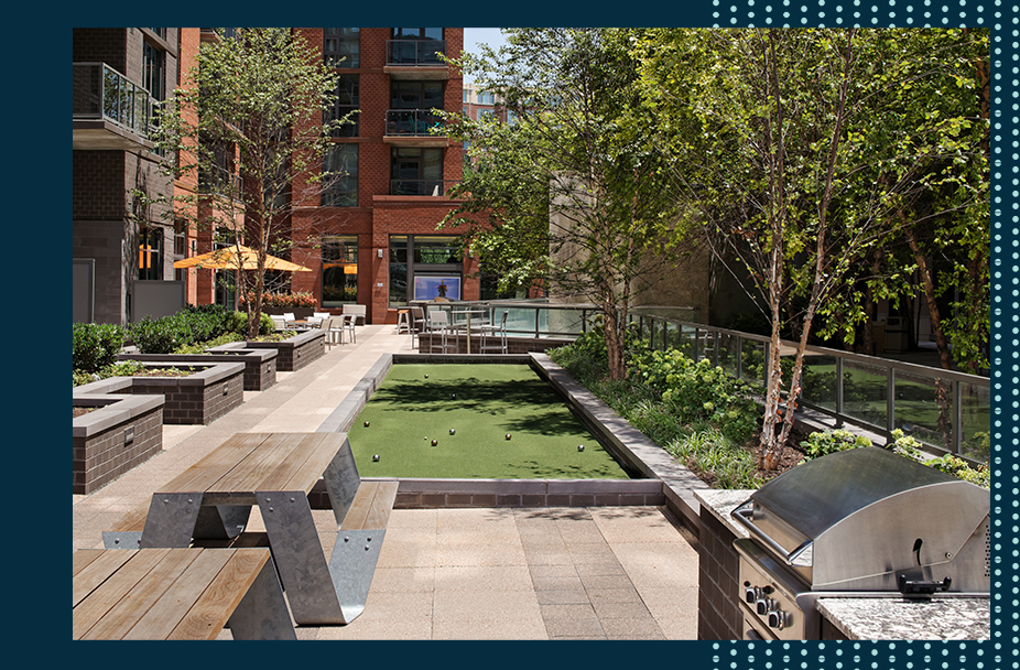 bocce court and outside courtyard at Parc Riverside apartments in Navy Yard DC with black frame that has teal polka dots on the right side