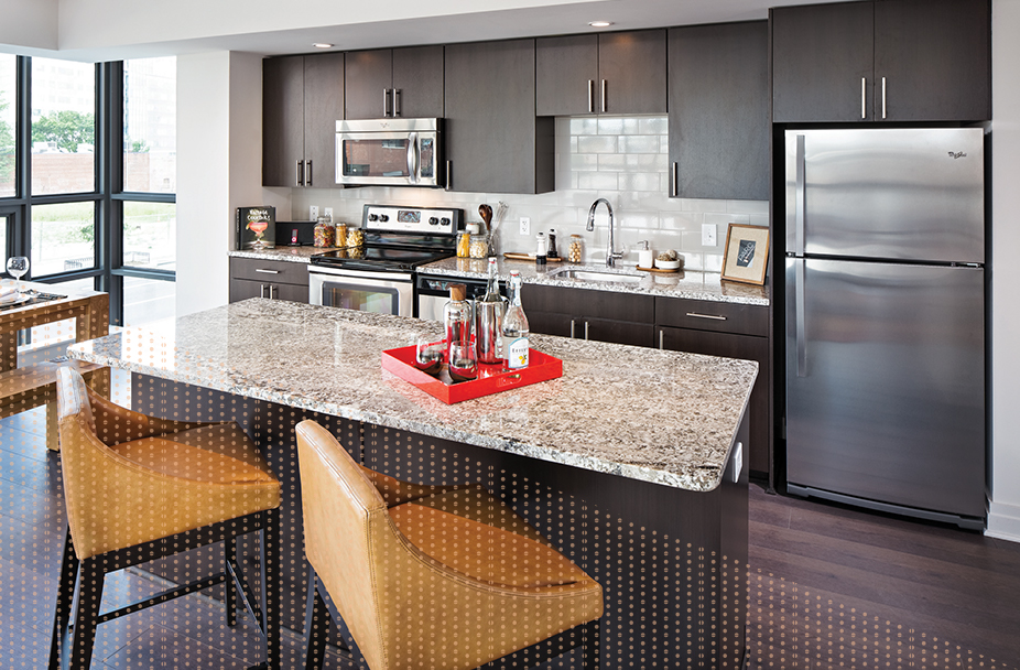 photo of modern kitchen at Parc Riverside apartments in Navy Yard DC. with dark wood cabinets, quartz counters and stainless steel appliances. There is a separate island with two hightop chairs across from the main counter area.