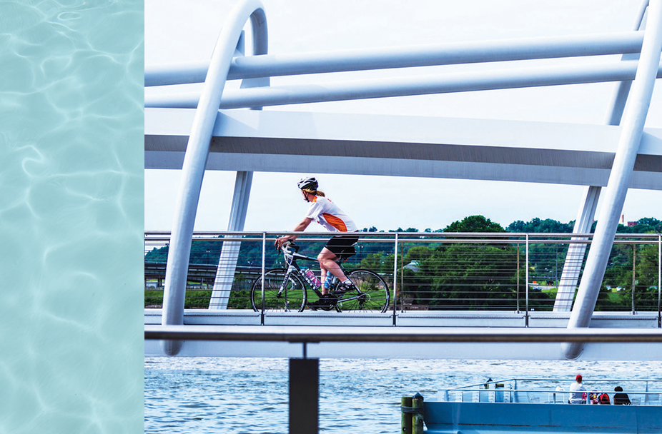photo of woman riding bicycle across bridge at the Capitol Riverfront in Washington, DC