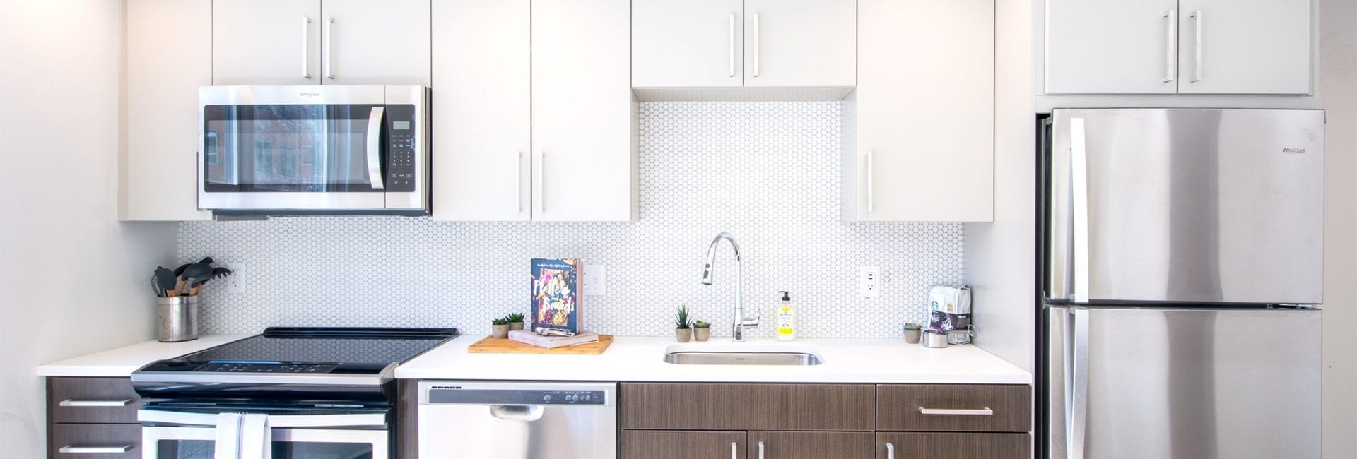 rendering of modern kitchen at Parc Riverside apartments in Navy Yard DC with white cabinets on top, dark brown cabinets on bottom and stainless steel appliances