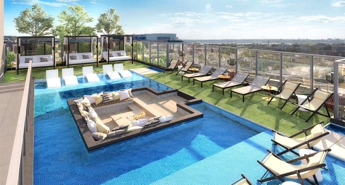 rendering of rooftop pool at Parc Riverside apartments in DC with pool surrounded by lounge chairs and hot tub and seating area that juts out into center of pool. View of DC in the background.